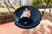 child with multi-disability, quadriplegic medical box play lying on big swing in a city park.  adapted park.  Relaxed and smiling.