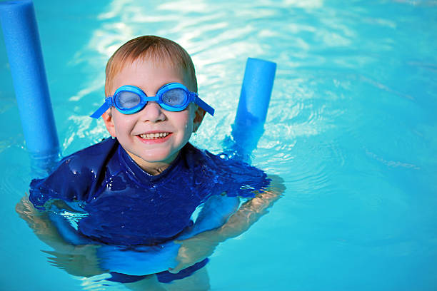 Child with Noodle Float and Swimming Goggles Learning to Swim stock photo