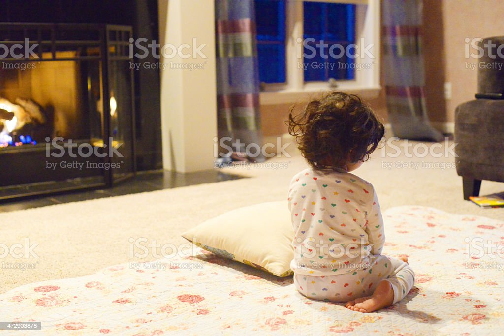 Child with pajamas on sitting on the floor by the fireplace stock photo