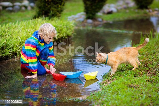 istock Child with paper boat in puddle. Kids by rain. 1159905800