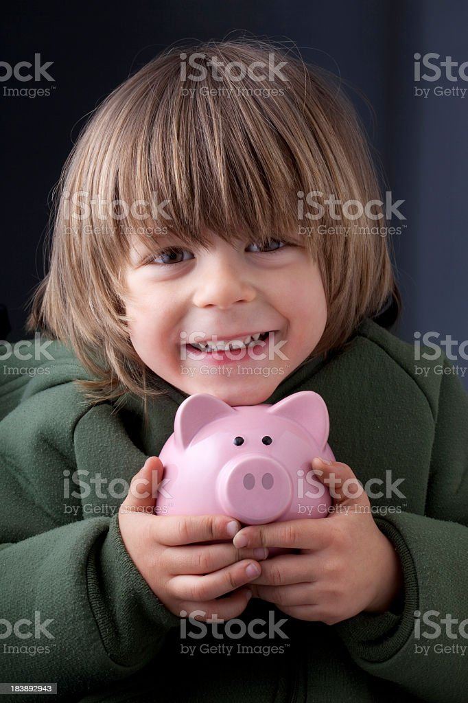 Child with piggy bank in his hands royalty-free stock photo