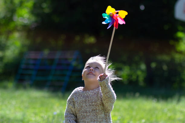 Child with Pinwheel in the summer park looking at the toy Child with Pinwheel in the summer park looking at toy weather vane stock pictures, royalty-free photos & images