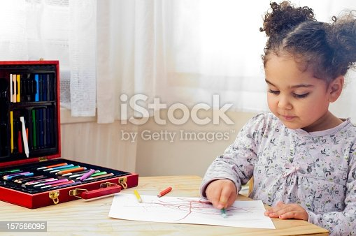 istock Child with pony tails drawing with colored crayons 157566095