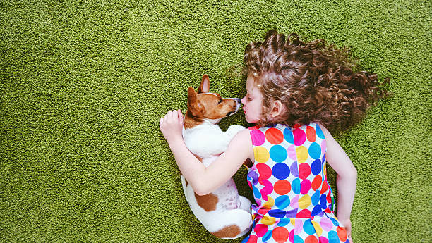 child with puppy dog sleeping on the green carpet. – Foto