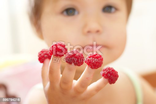 Little kid with raspberry on fingers, focus on hands