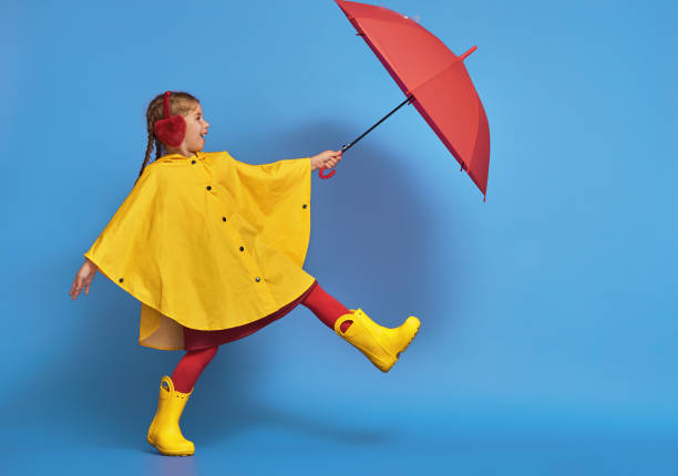 child with red umbrella Happy funny child with red umbrella posing on blue wall background. Girl is wearing yellow raincoat and rubber boots. waterproof clothing stock pictures, royalty-free photos & images