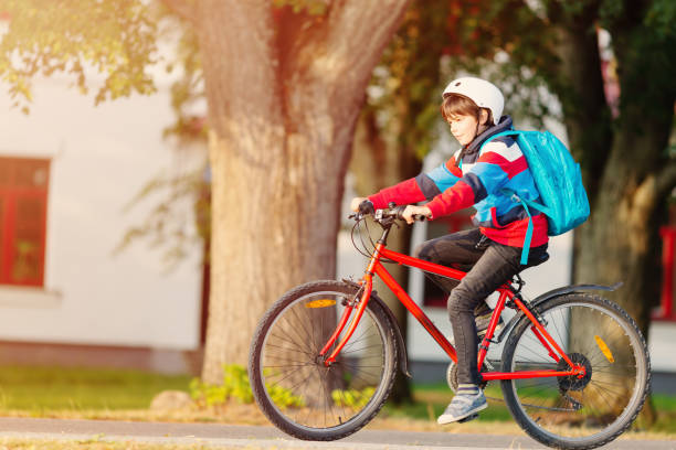 Child with rucksack riding on bike in the park near school stock photo
