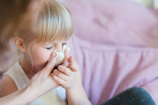 child with runny nose. mother helping to blow kid's nose with paper tissue. seasonal sickness - illness stock pictures, royalty-free photos & images