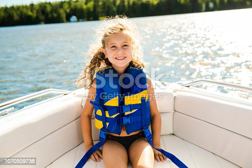 A child with safety vest on the lake boat