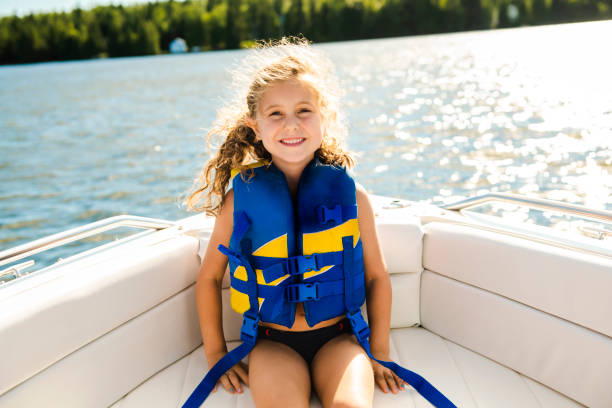 child with safety vest on the lake boat stock photo