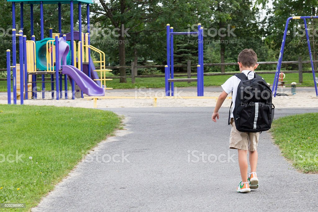 Child with school backpack and book walking in the park stock photo