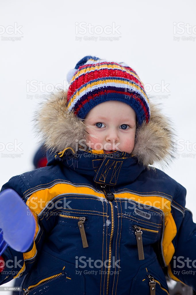 child with shovel look at you in winter background royalty-free stock photo