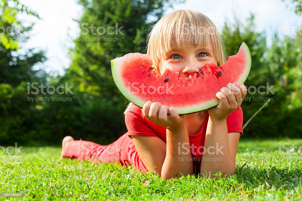 Child with slice of melon outdoor stock photo