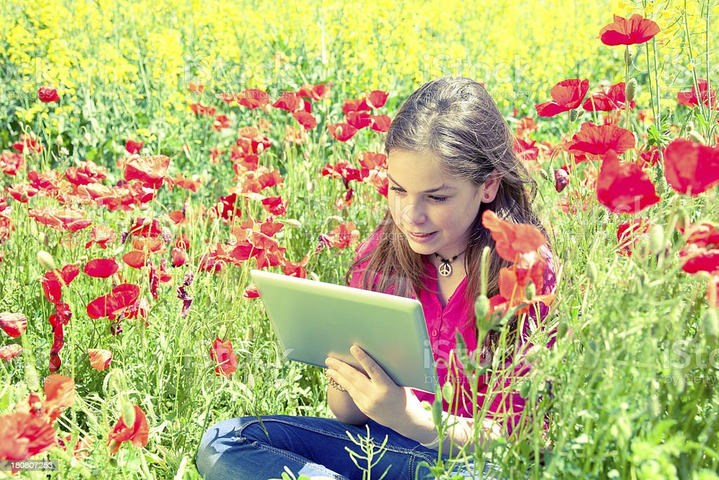 Child with tablet among flowers royalty-free stock photo