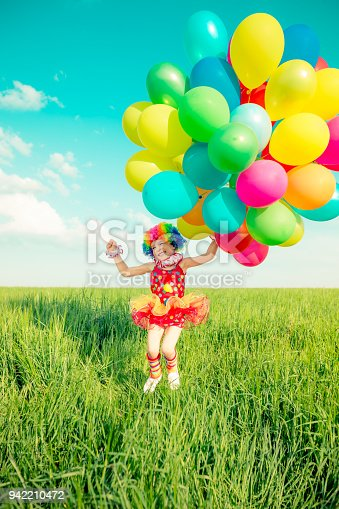 istock Child with toy balloons in spring field 942210472