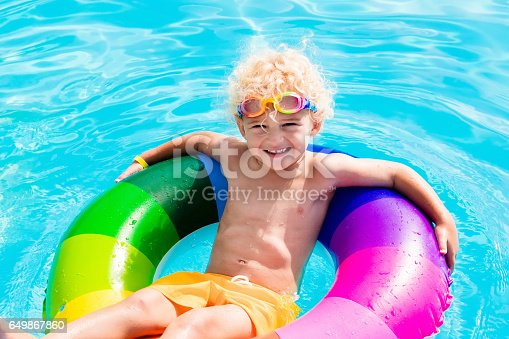 istock Child with toy ring in swimming pool 649867860