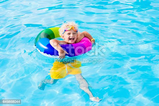 istock Child with toy ring in swimming pool 649868044