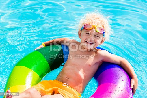 istock Child with toy ring in swimming pool 663887822