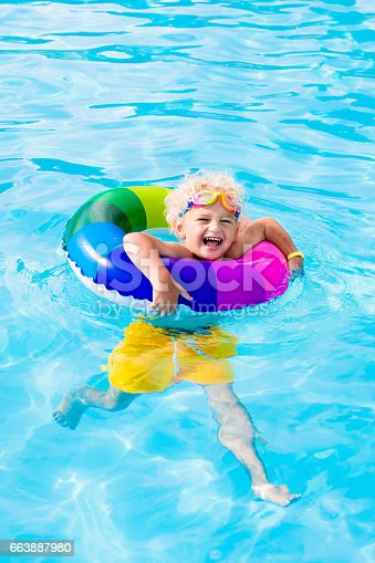 istock Child with toy ring in swimming pool 663887980