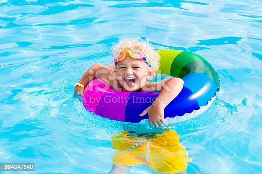 istock Child with toy ring in swimming pool 664047640