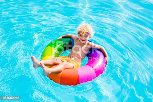 istock Child with toy ring in swimming pool 664050948