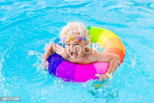 istock Child with toy ring in swimming pool 667274066