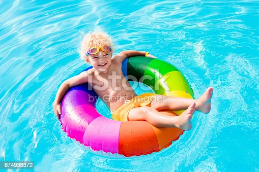 istock Child with toy ring in swimming pool 674938372