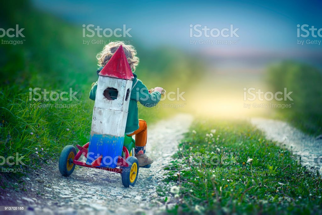 Child With Toy Space Rocket and Tricycle stock photo