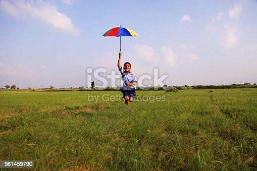 Child standing in nature holding umbrella.