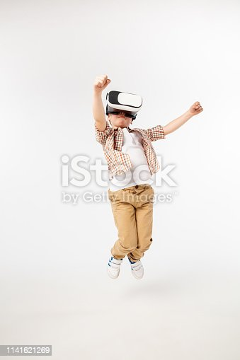 istock Child with virtual reality headset 1141621269