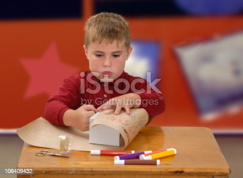 Child at school making gift paper and wrapping a box
