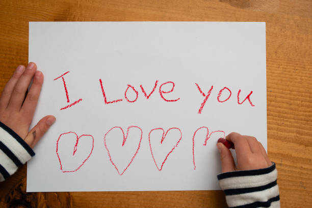 Child writes i love you on paper stock photo