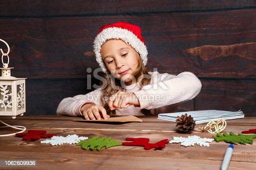 1062609644istockphoto Child writes letter to Santa Claus . Funny girl in Santa hat writes letter to Santa at home 1062609936