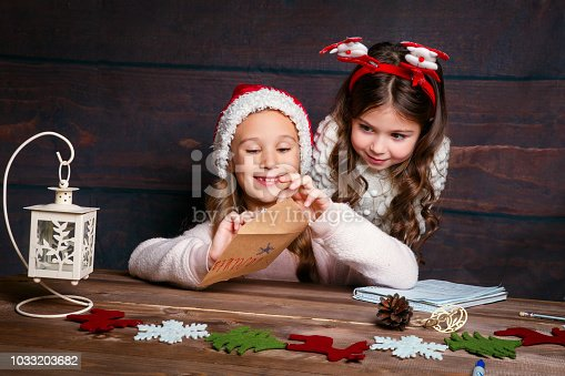 istock child writes letter to Santa Claus . Funny girls in Santa hat writes letter to Santa 1033203682