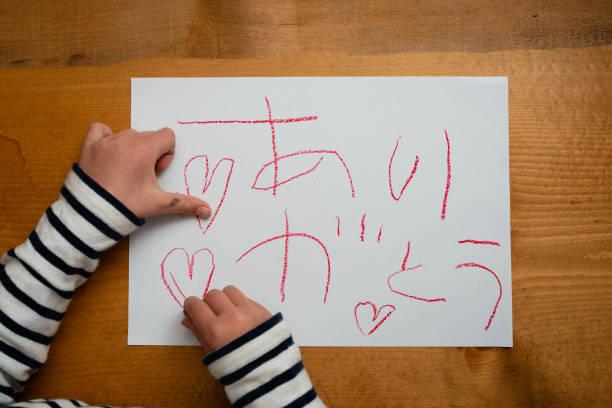 kind schreibt dankeswort auf japanisch - kreatives schreiben übungen stock-fotos und bilder