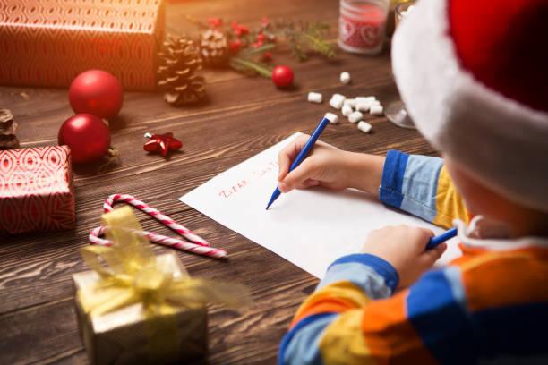 Child writes the letter to santa claus on wooden background with picture id1068391962?b=1&k=6&m=1068391962&s=612x612&w=0&h=vtg9jajysrmktzwhvuphbapoybtbfas ol9jdqxeyrw=