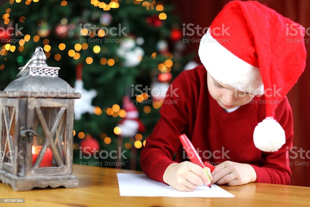 A young boy wearing a red Christmas hat is writing a letter to Santa...