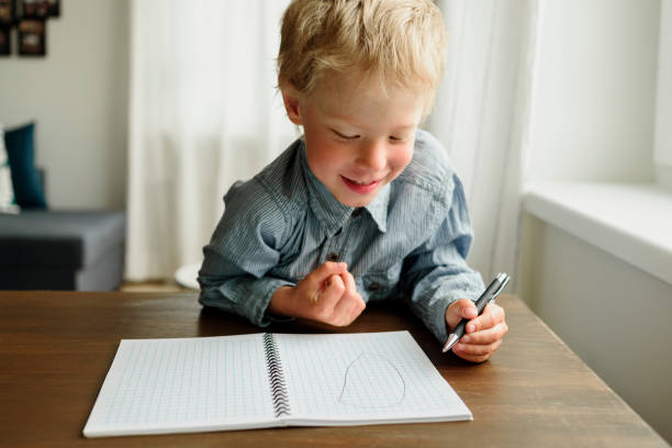 Child writing by left hand in notepad