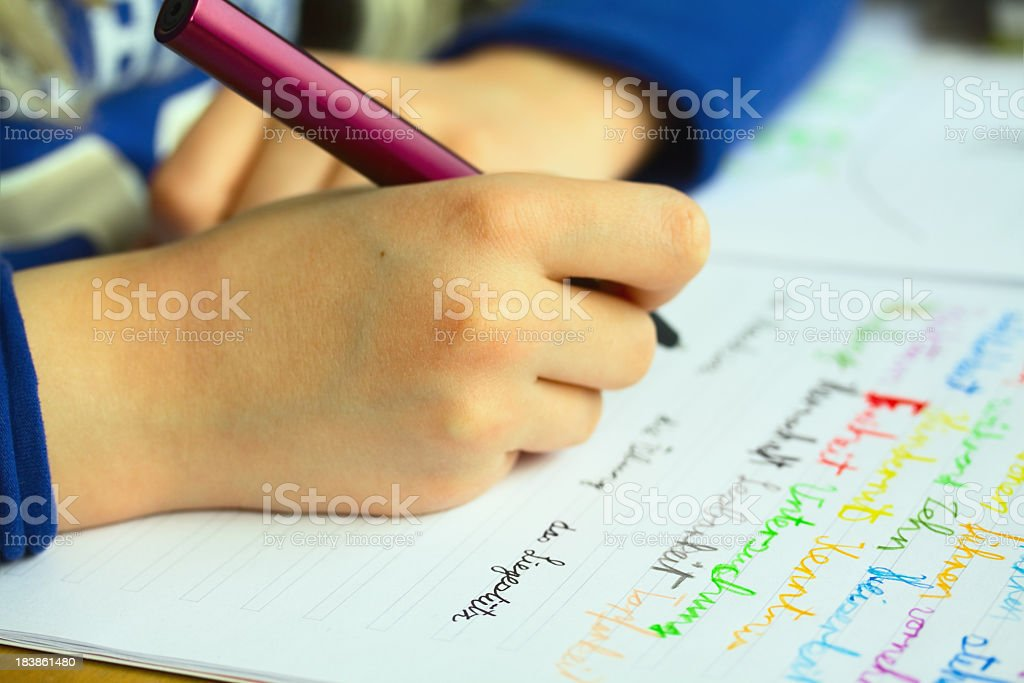 A child writing in their school book with a pen stock photo