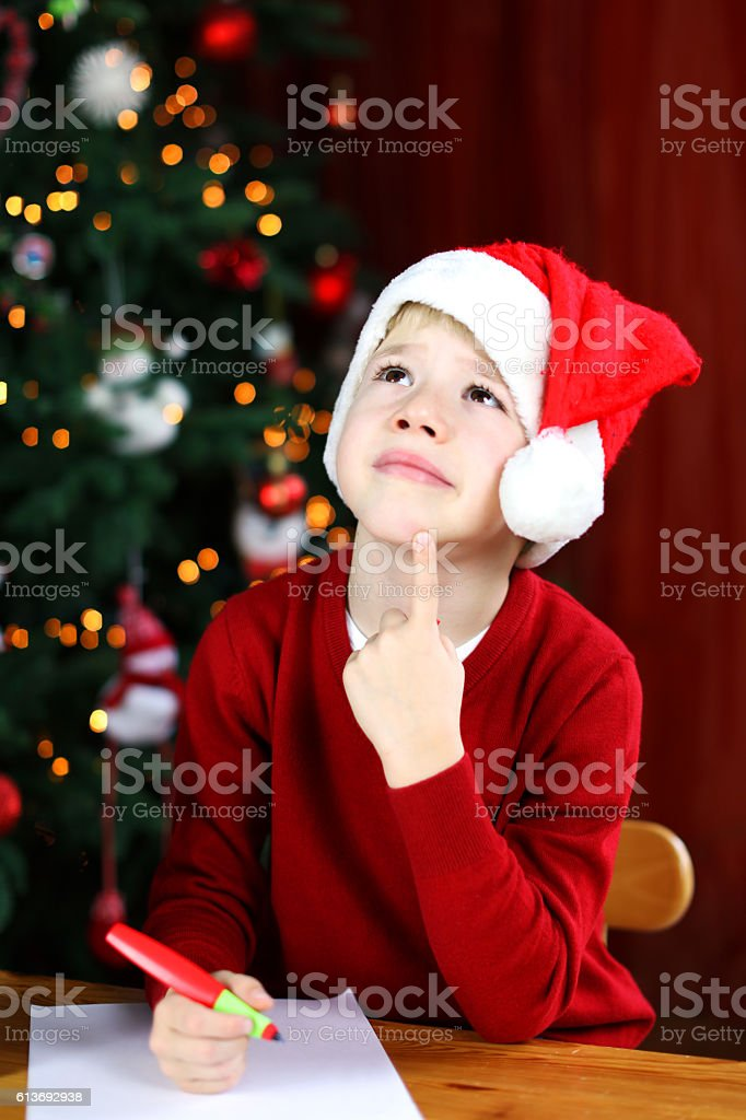 Child Writing Letter to Santa Claus Thinking What to Ask stock photo