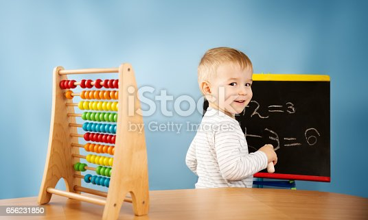 istock Child writing numbers on chalkboard 656231850