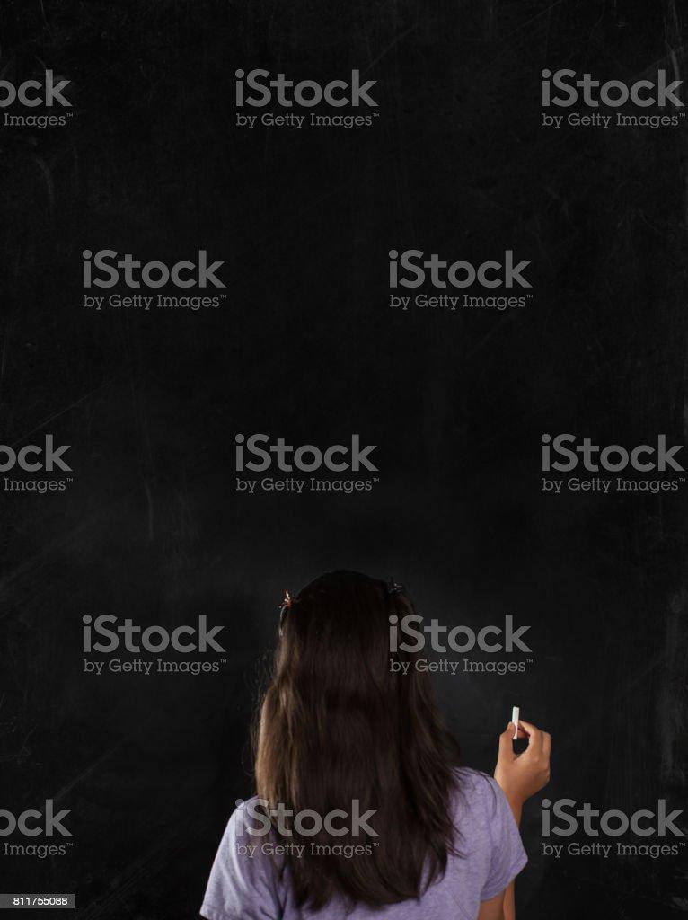 child writing on chalk board stock photo