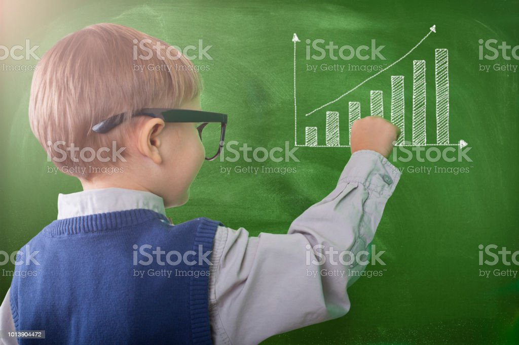 Child writing on chalkboard stock photo