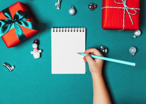 kind einen brief an den weihnachtsmann schreiben. weihnachts-geschenk-boxen auf blauem hintergrund eingefroren. - eco bastelarbeiten stock-fotos und bilder