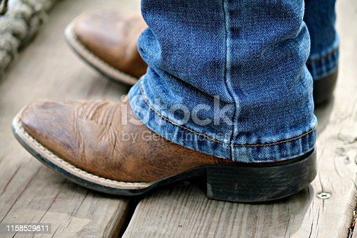 Youth wearing cowboy boots and blue jeans stands on wood deck flor near rope bridge