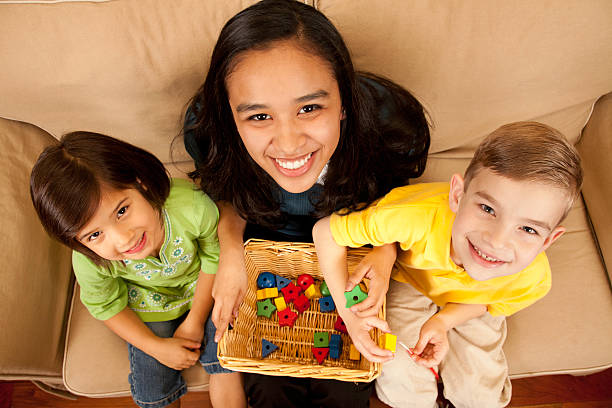 Childcare Baby Sitter with Two Children stock photo