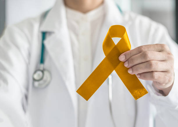 Childhood cancer awareness with gold ribbon symbolic bow color in doctor's hand Childhood cancer awareness with gold ribbon symbolic bow color in doctor's hand alveolar duct stock pictures, royalty-free photos & images