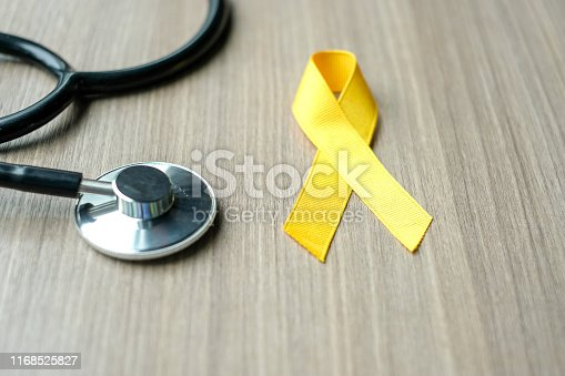 istock Childhood Cancer Awareness, Yellow Ribbon with stethoscope  for supporting people living and illness. children Healthcare and World cancer day concept 1168525827