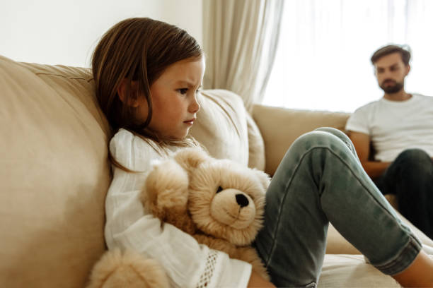 Childhood. Education. Problem. Sad little girl is hugging her teddy bear, her father in the background Childhood. Education. Problem. Sad little girl is hugging her teddy bear, her father in the background punishment stock pictures, royalty-free photos & images
