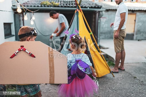 Happy children wearing costumes. Girl is butterfly, while boy is airplane. They are outdoors. Waiting for their party to be prepared.
